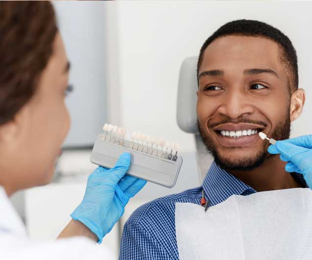 dentist checking a man's teeth color for a cosmetic dentistry treatment