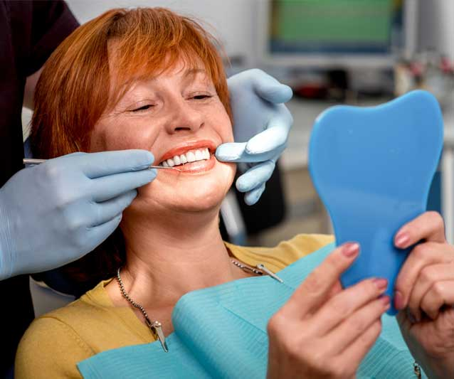 patient checking her teeth after getting dentures