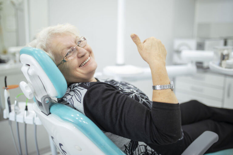woman showing thumbs up while getting dentures at a dentist's office